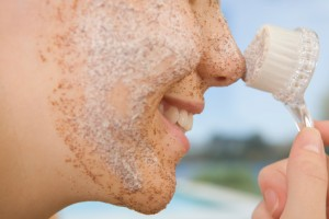 Close-up of a young woman applying facial mask with a brush